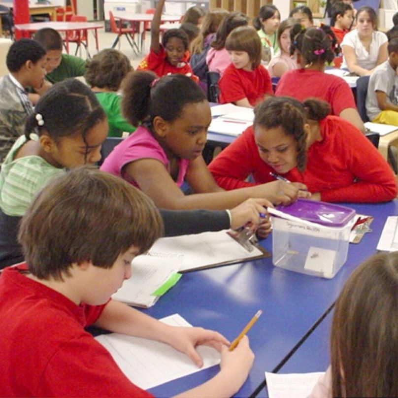 Middle school science students working at a table